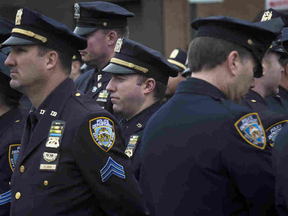 Police officers turn their backs as Mayor Bill de Blasio speaks during the funeral of New York Police Department Officer Wenjian Liu at Aievoli Funeral Home Sunday.