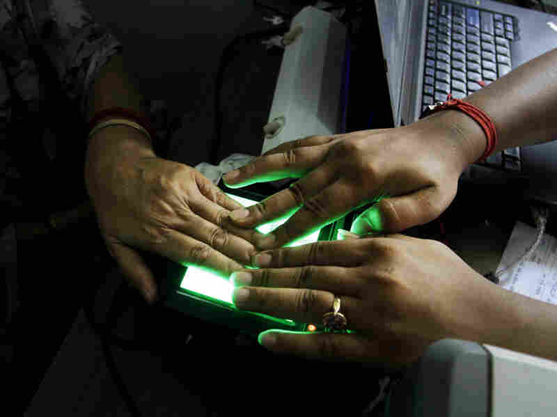 An operator helps an elderly woman scan her fingerprints in May 2012 as she enrolls in an identification project called Aadhar in India. The giant effort, which aims to give every Indian an identity record and number for the first time, involves recording retina scans, fingerprints and photographs of all 1.2 billion Indians.