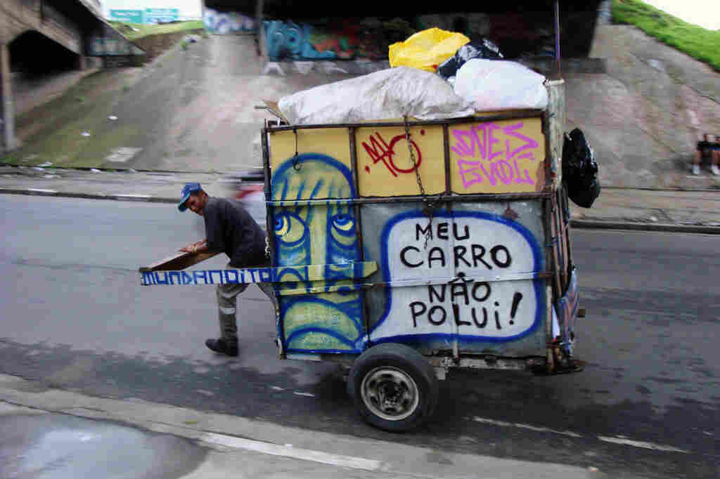 """A waste picker wheels a trash cart with Mundano's art and spreads the word: """"My cart doesn't pollute."""""""