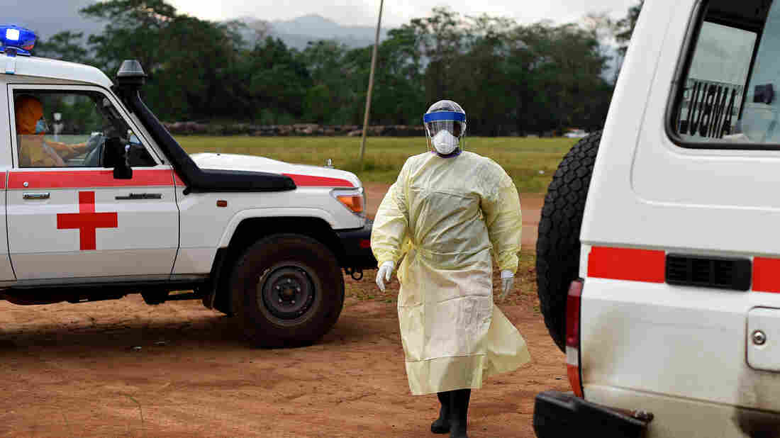 A health worker, wearing personal protective equipment, returns to her ambulance after transporting a patient to the Hastings treatment center outside Freetown. The center is the only one run exclusively by locals.