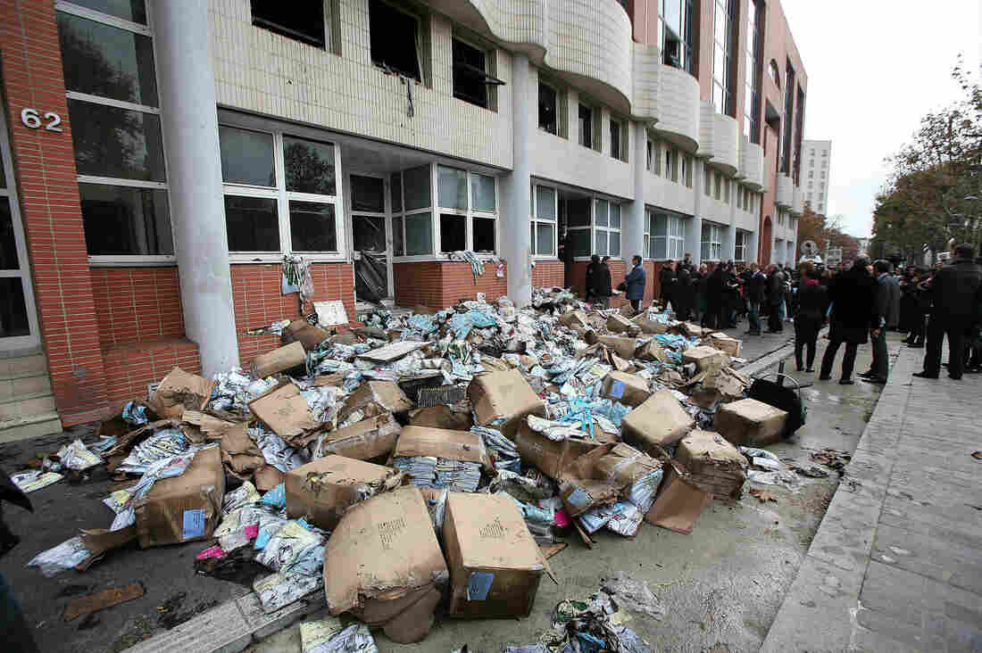"Fire-damaged objects are scattered outside Charlie Hebdo offices following the firebombing in 2011. The attack, which completely destroyed the offices, came a day after the magazine featured a caricature of the Prophet Muhammad on its cover and named him ""editor-in-chief."""