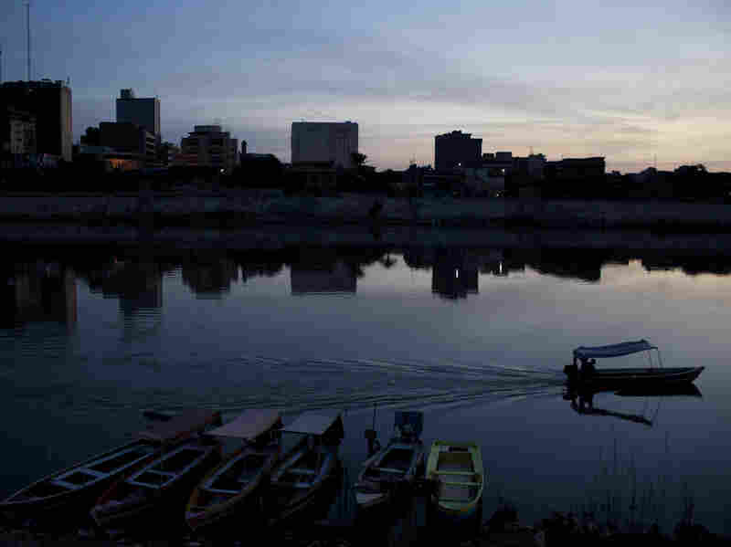 A fisherman drives his motorboat on the Tigris River at dawn on March 29, 2013, in Baghdad, Iraq, ten years after the regime of Saddam Hussein was toppled from power.