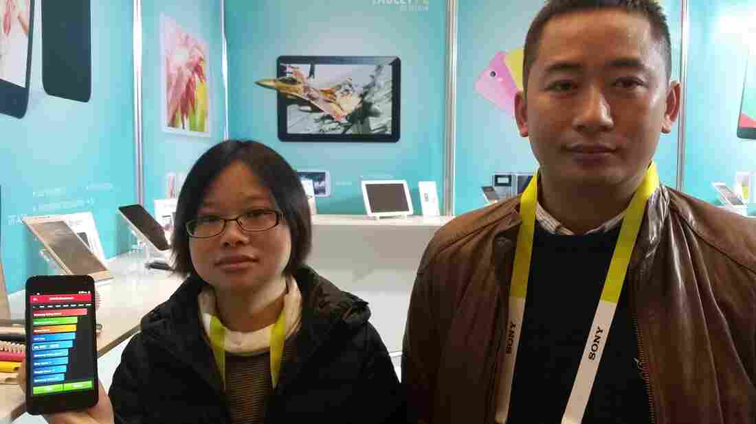 Irene Chen and Longlai Zuo, with the China-based company Quality Technology Industrial, show off their top-line phones, which cost about $100.