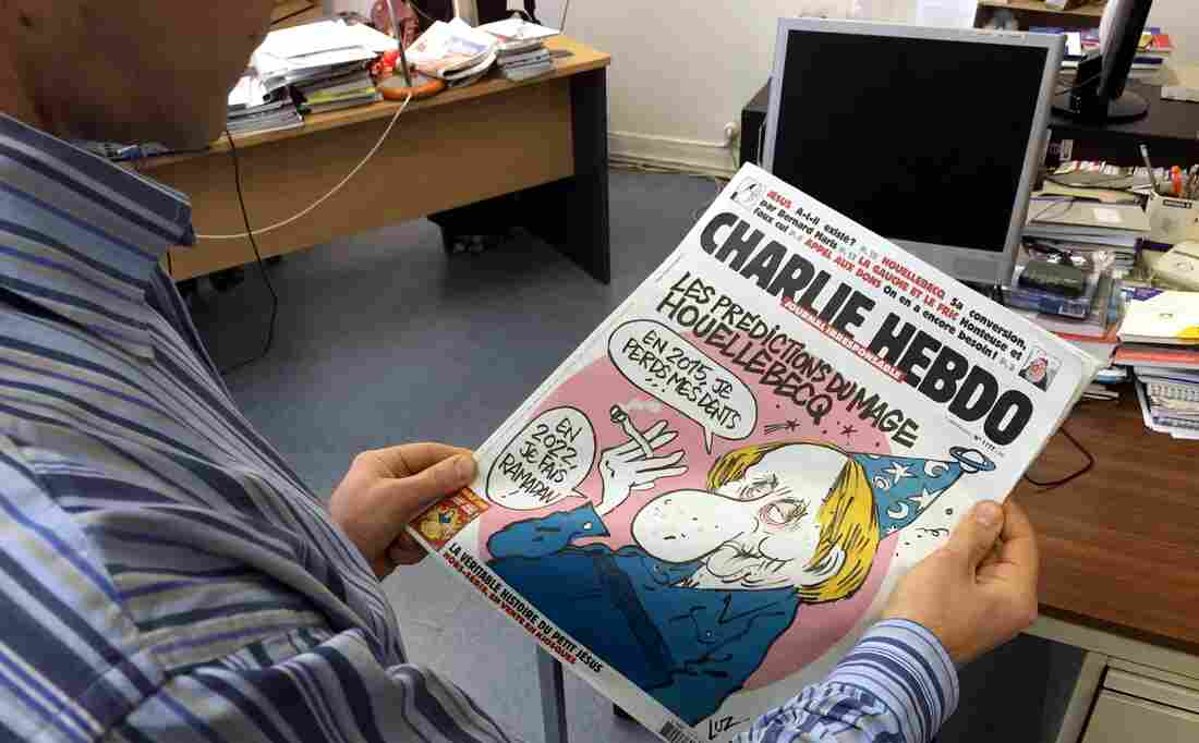 A journalist views the front page of the latest issue of Charlie Hebdo on Wednesday.