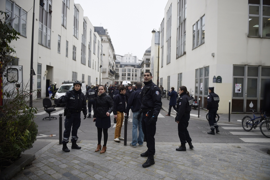 Police forces gather in street outside the offices of the French satirical weekly <em>Charlie Hebdo</em> in Paris on Wednesday, after armed gunmen stormed the offices. (Martin Bereau /AFP/Getty Images)