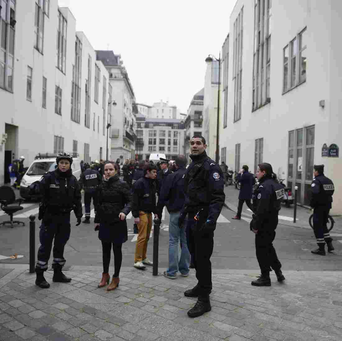 Police forces gather in street outside the offices of the French satirical weekly Charlie Hebdo in Paris on Wednesday, after armed gunmen stormed the offices.