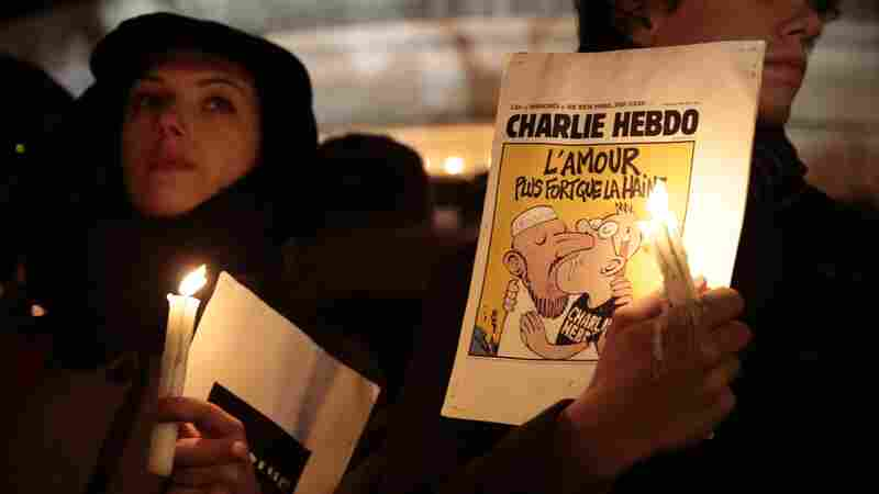 A man holds a cartoon published by Charlie Hebdo during a gathering at Republic Square in Paris on Wednesday, to show solidarity for victims of the attack on the offices of the satirical weekly.