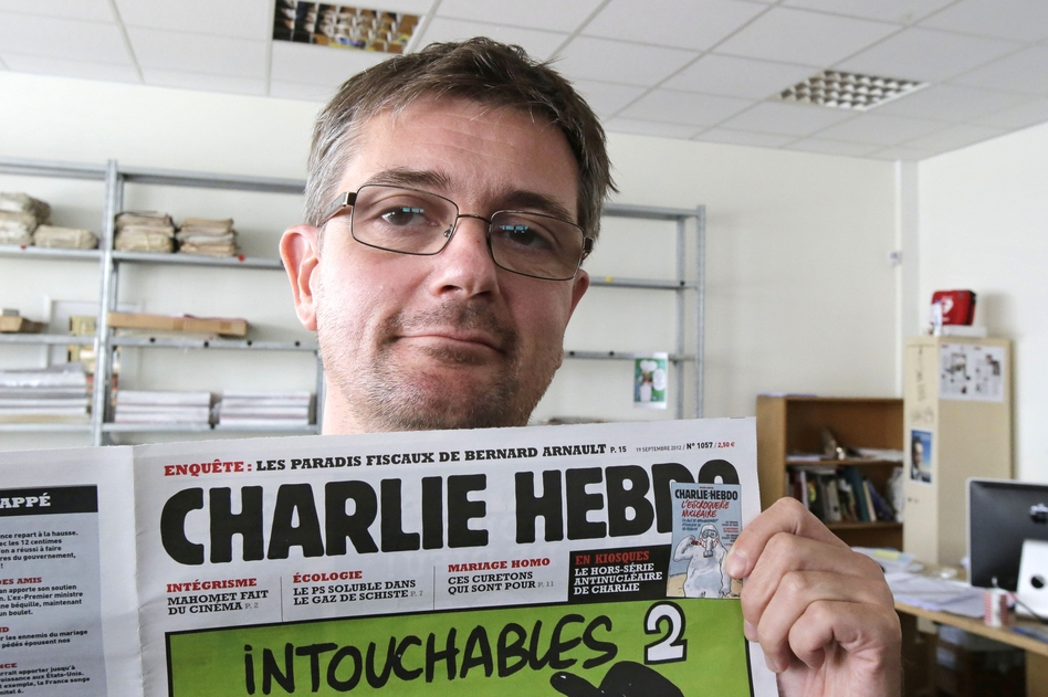 Stephane Charbonnier, the editor of <em>Charlie Hebdo, </em>poses with his magazine on Sept. 19, 2012. The magazine, which was attacked today, is part of a long tradition of French satire. (Michel Euler/AP)