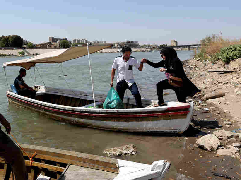 An Iraqi man helps his wife onto a boat across the Tigris River on Sept. 18 in central Baghdad. Many civilians use small boats to cross the Tigris river and avoid the traffic jams and possible attacks on the roads.