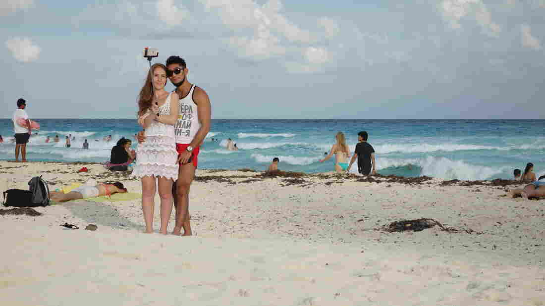 A couple uses a selfie stick on a Mexican beach.