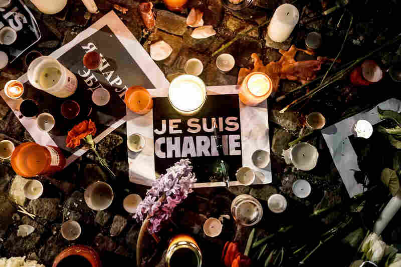 "Papers reading ""Je Suis Charlie"" — ""I am Charlie"" — are left near candles at a vigil in front of the French Embassy in Berlin."