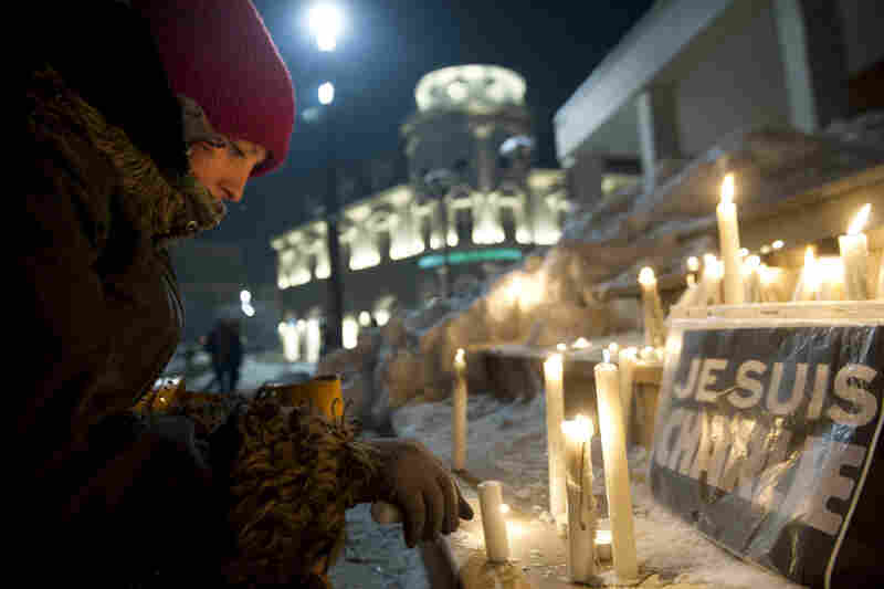 """A Kosovo Albanian woman lights a candle next to an """"I am Charlie"""" sign during a gathering in Pristina."""