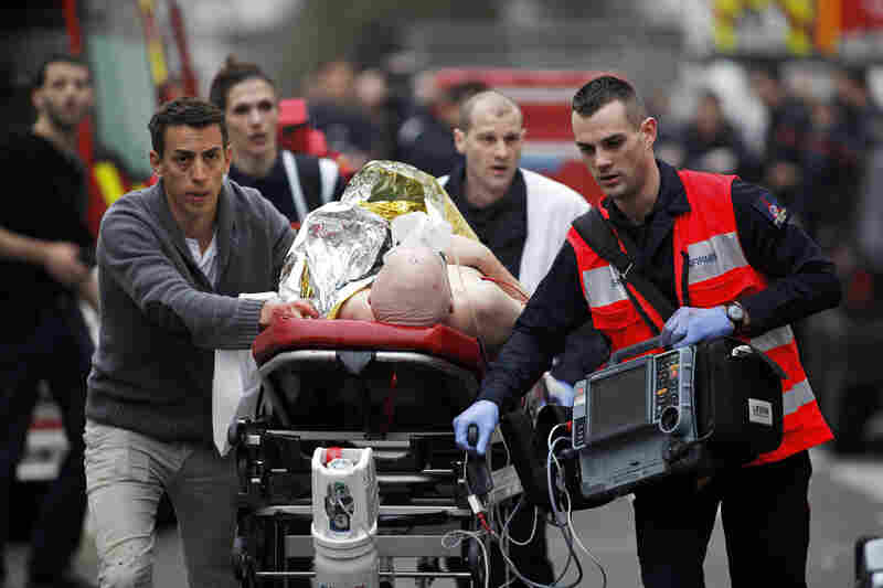 An injured person is evacuated outside the office. In 2011, Charlie Hebdo was the target of a firebomb attack after it printed a drawing of the Prophet Muhammad.