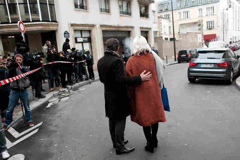 People stand outside the Charlie Hebdo office after the attack. NPR's Eleanor Beardsley says it's unclear how the gunmen managed to get past extra security, which had been put in place because of previous threats.