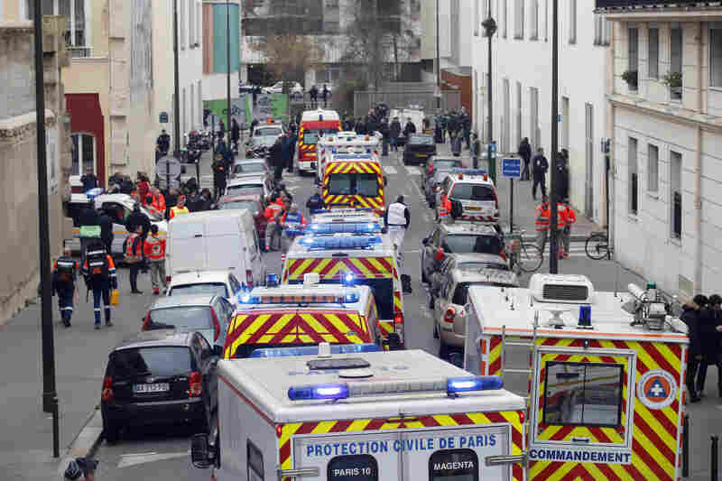 """Ambulances gather in the street outside the Charlie Hebdo office in Paris. Hollande promised that """"everything will be done to capture the perpetrators"""" and bring the gunmen to justice."""