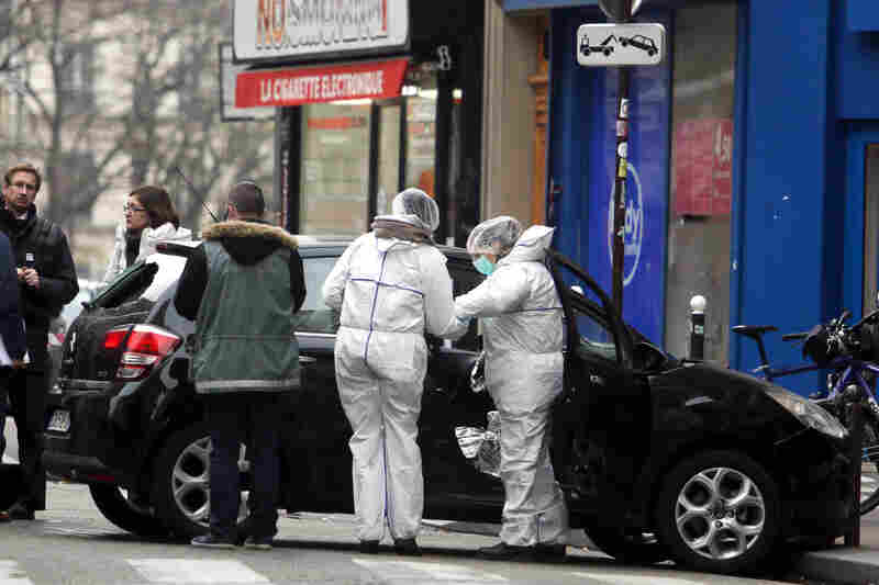 Forensic experts examine a car believed to have been used as an escape vehicle by the assailants. Four of the magazine's founding cartoonists were killed in the attack, according to French news outlets. Eleven other people were injured, four of whom are in critical condition.
