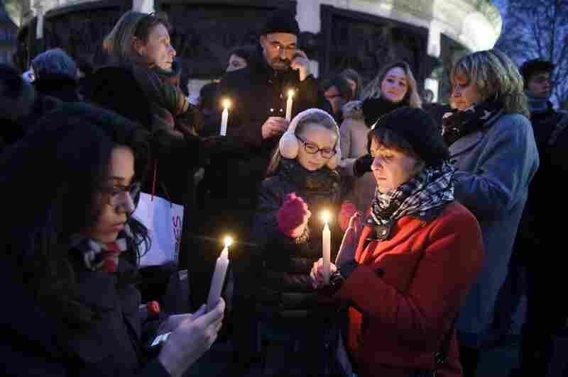 People light candles during a vigil at the Place de la Republique in Paris.