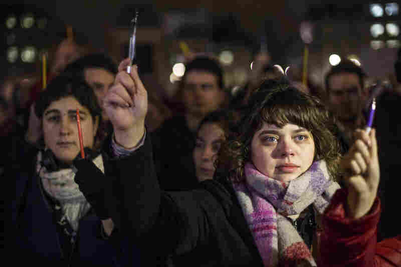 People hold up pens during a vigil in London's Trafalgar Square.