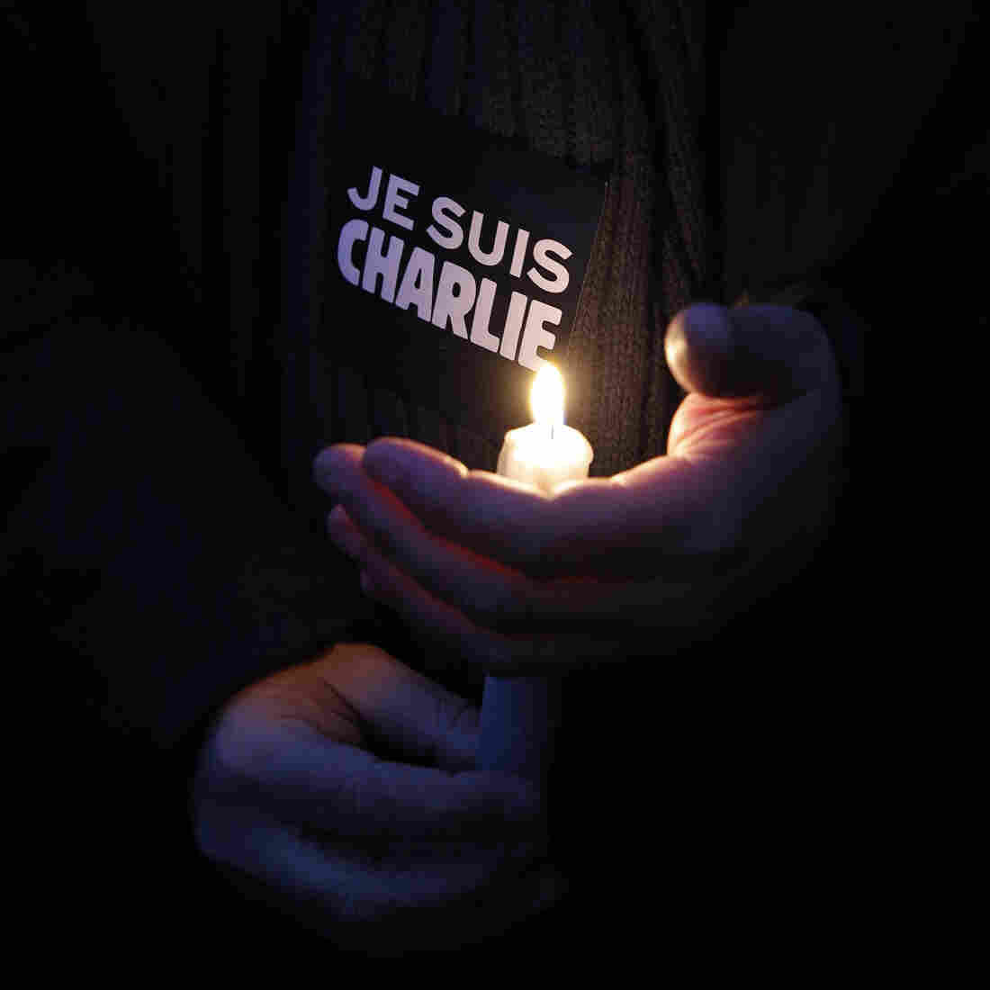 "A man holds a candle and a sticker reading ""I am Charlie"" during a demonstration in Paris on Wednesday."