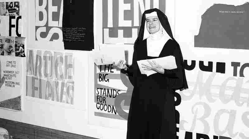 Sister Corita Kent stands in front of her work, including for eleanor, at Immaculate Heart College in 1964.