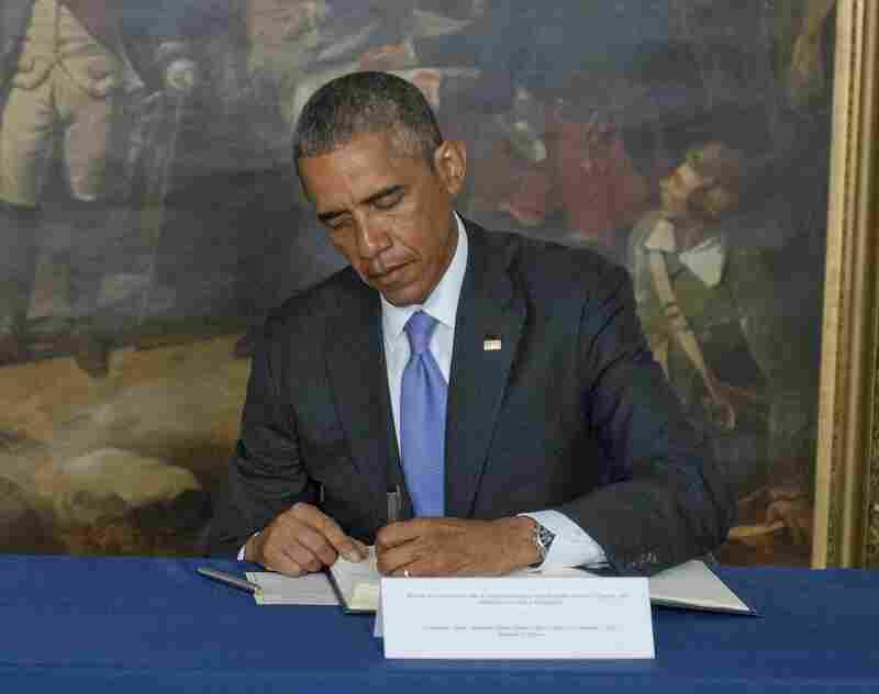 President Barack Obama signs a book of condolence for those killed in the attack on the offices of Charlie Hebdo magazine. Obama visited the Embassy of France in Washington Thursday.