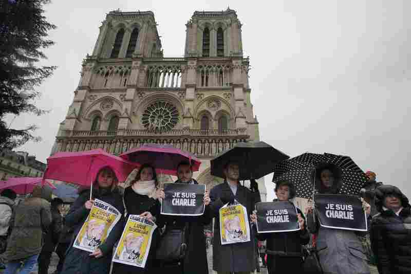 "People hold signs reading ""I am Charlie"" during the moment of silence at the Notre Dame Cathedral."