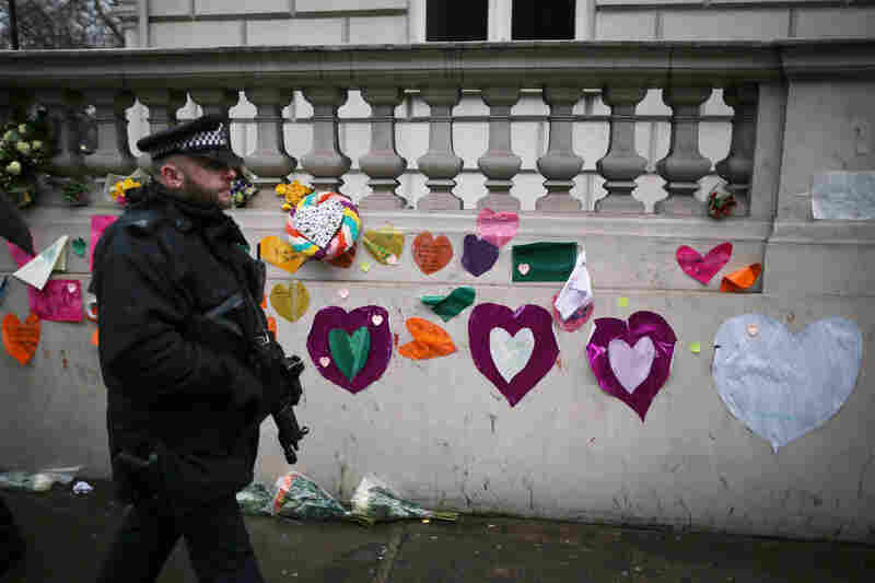 A police officer in London walks past a wall covered with sympathy messages at the French Embassy.