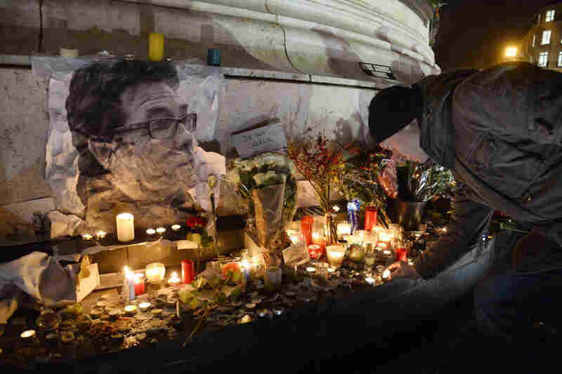 "A man lights a candle next to a picture of French cartoonist Bernard ""Tignous"" Verlhac during a rally at Republic Square in Paris on Thursday. The cartoonist was one of 12 people killed in an attack Wednesday on the headquarters of the satirical magazine Charlie Hebdo."