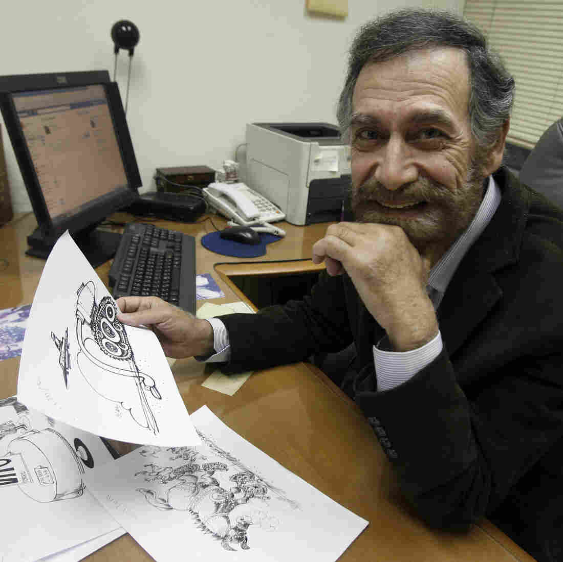 Syrian political cartoonist Ali Farzat sits at his desk at a Kuwaiti newspaper on Dec. 14, 2011. Earlier that year, Farzat was badly beaten in retaliation for cartoons that mocked Syrian President Bashar Assad.