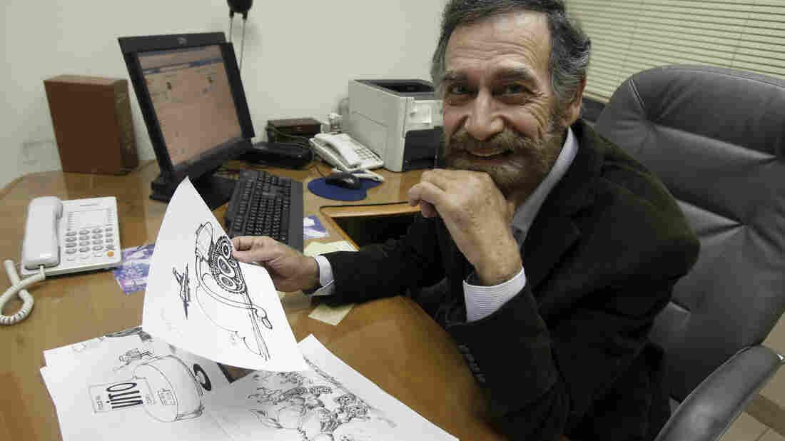 Syrian political cartoonist Ali Farzat sits at his desk at a Kuwaiti newspaper on Dec. 14, 2011. Earlier that year, Farzat was badly beaten in retaliation for cartoons that mocked Syrian President Bashar Assad.
