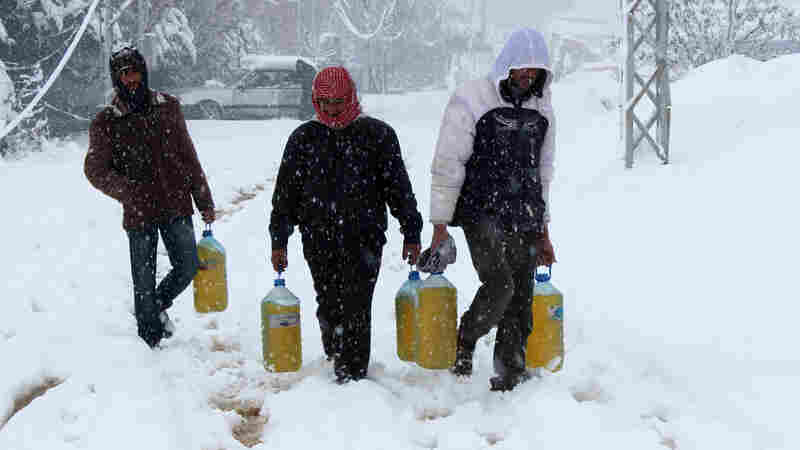 Syrian refugees carry gasoline under heavy snow fall at the a U.N.-run refugee camp of Fayda near the Bekaa Valley town of Zahle in eastern Lebanon on Jan. 7.