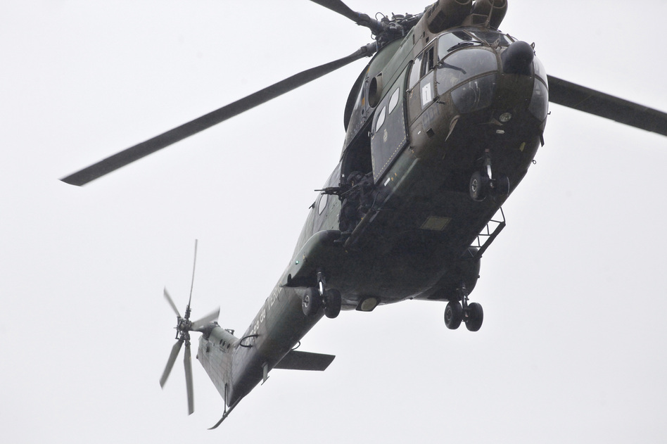 Armed security forces fly overhead in a military helicopter in Dammartin-en-Goele, northeast of Paris, on Friday. (Thibault Camus/AP)