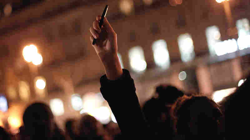 In Paris late Wednesday, a woman held a pen in the air during a memorial. Hundreds gathered to show solidarity with the cartoonists at Charlie Hebdo, where gunmen killed 12 people.