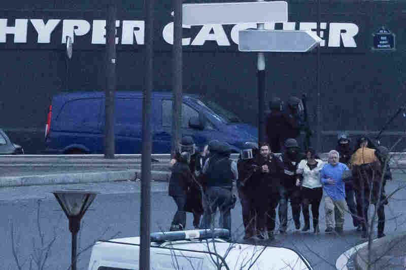 Security officers escort people away from a kosher market that was stormed by police Friday in Paris. A gunman who allegedly has ties to the suspects in Wednesday's attack on a French satirical magazine had entered the market and reportedly taken hostages.