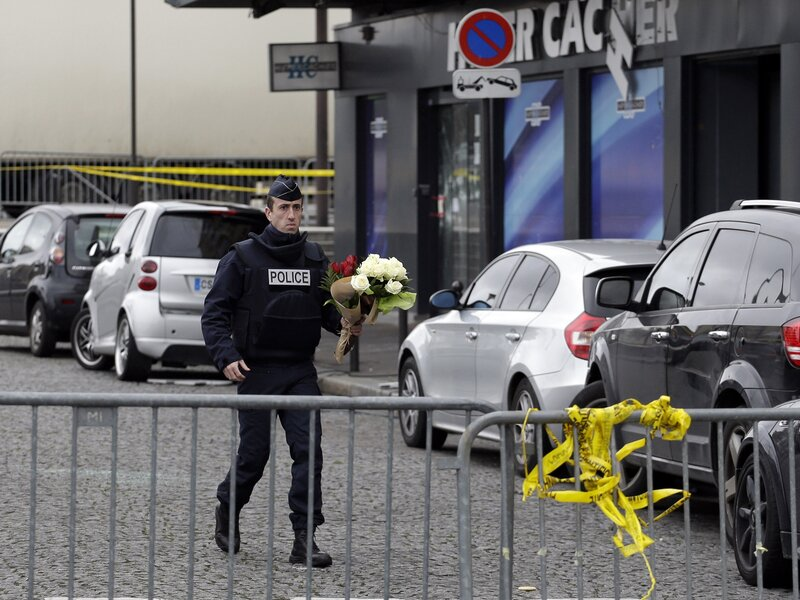 A police officer carries flower tributes at the site of Friday's attack on a kosher market in Paris, France.
