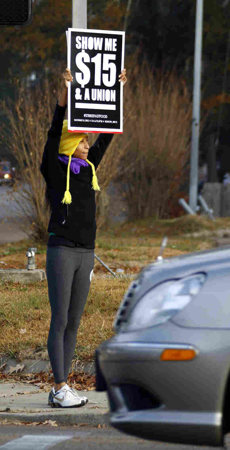A protester demonstrates for higher wages for fast food workers in Jackson, Miss., in December. Employers are hiring more people, but overall, the wages they're paying remain flat.