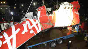 Crew members of Crest Onyx ship and Members of National Search And Rescue Agency unload the wreckage of part of the ill-fated AirAsia Flight 8501 on Sunday.