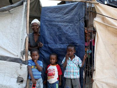 A family looks out from behind the tarp that serves as the front door to their home. The structure was built five years ago over the land where their home stood before the 2010 earthquake. At one point, about 1.5 million people lived in tents across Haiti. Now about 80,000 people live in these structures.