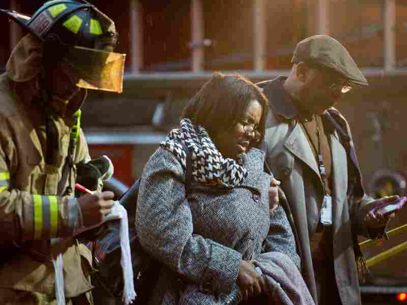 Smoke inhalation victims walk past a firefighter towards a medical aid bus Monday after passengers on the Washington, D.C., subway were injured when smoke filled the L'Enfant Plaza station during the afternoon rush hour.