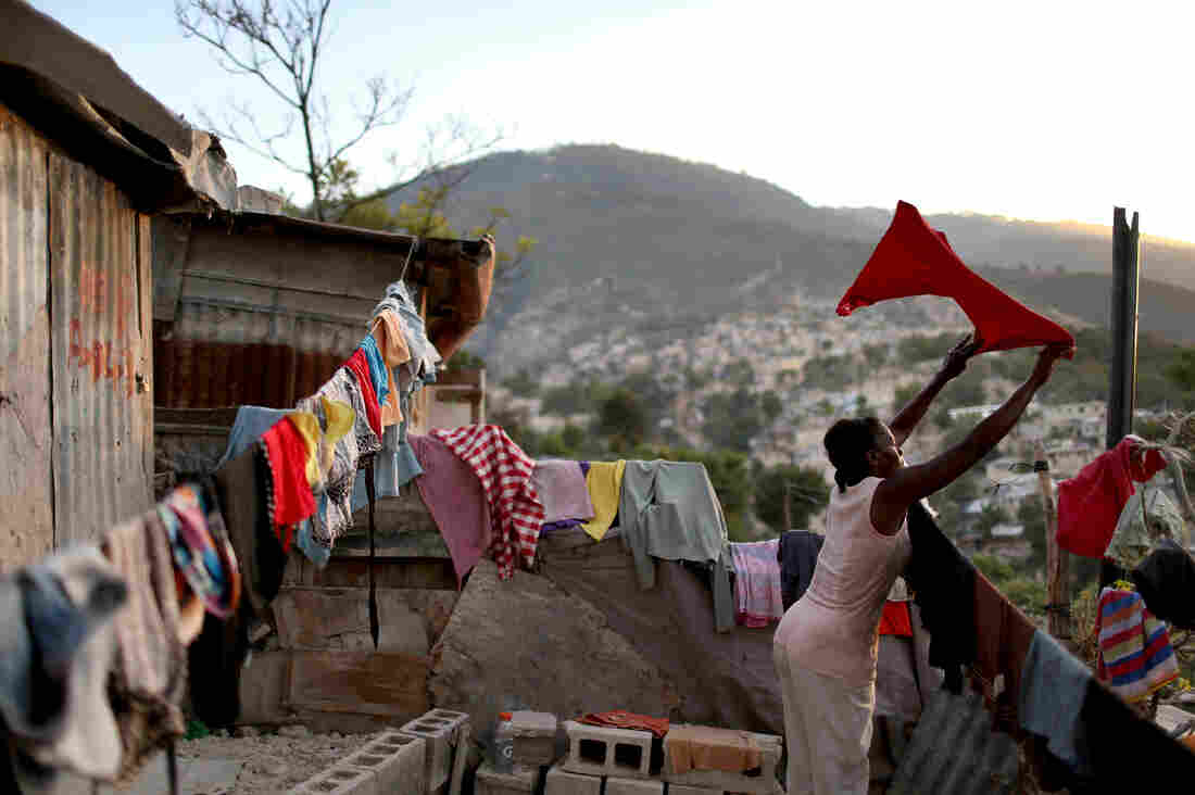 A woman in Port-au-Prince, Haiti, hangs her laundry to dry in front of her home. Her family made the shelter out of tin and tarps on land where their home stood before a massive earthquake devastated the nation in 2010. An estimated 80,000 Haitians displaced by the quake remain in tents.