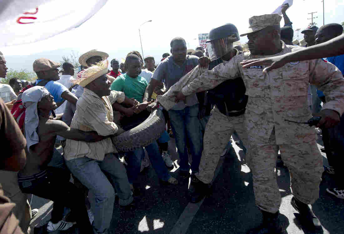 Haitian police try to take a tire from protesters Thursday during a march against the government of Haitian President Michel Martelly in Port-au-Prince. Protesters marched through the streets calling for the resignation of the Haitian leader.
