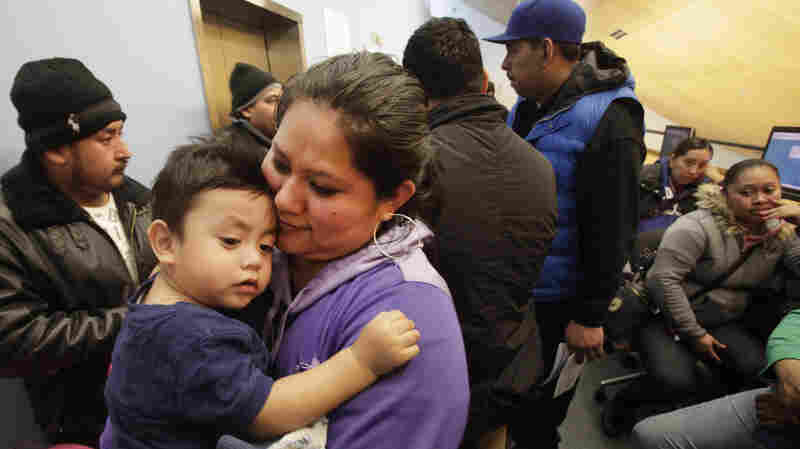 Veronica Ramirez holds her 15-month-old son, Lora, as she waits in line Monday to apply for a new municipal identification card at the Bronx Library Center in New York.