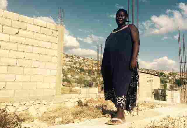 Displaced by the quake, Carline Lomil and her family now live with a relative in Canaan, in the dusty, rocky hillsides outside Port-au-Prince, while they build their own home nearby. Here, Lomil, who is pregnant, stands in the unfinished house. She works on it whenever they have money.
