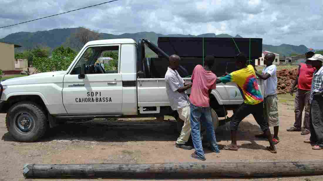 A total of 69 people died this weekend after drinking traditional beer in northwestern Mozambique. Here, men load the coffins of victims onto a pickup truck at the Chitima health center in Tete province Sunday.