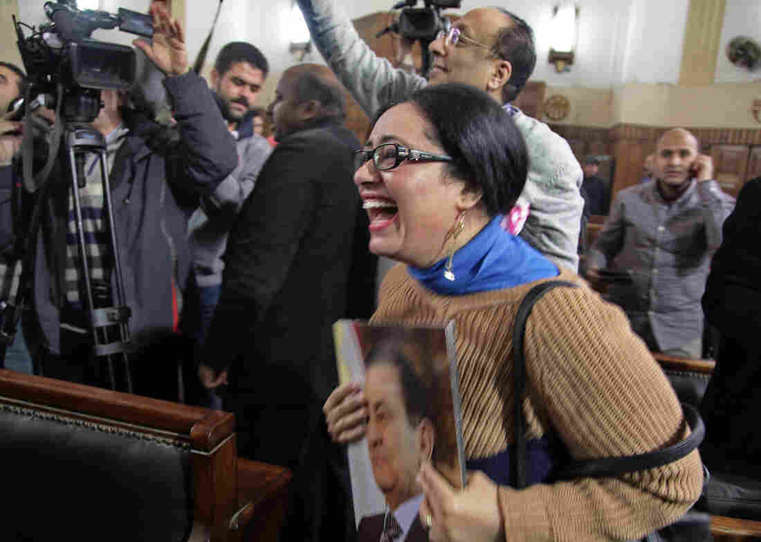 A supporter of ousted President Hosni Mubarak reacts to the verdict Tuesday ordering a retrial.