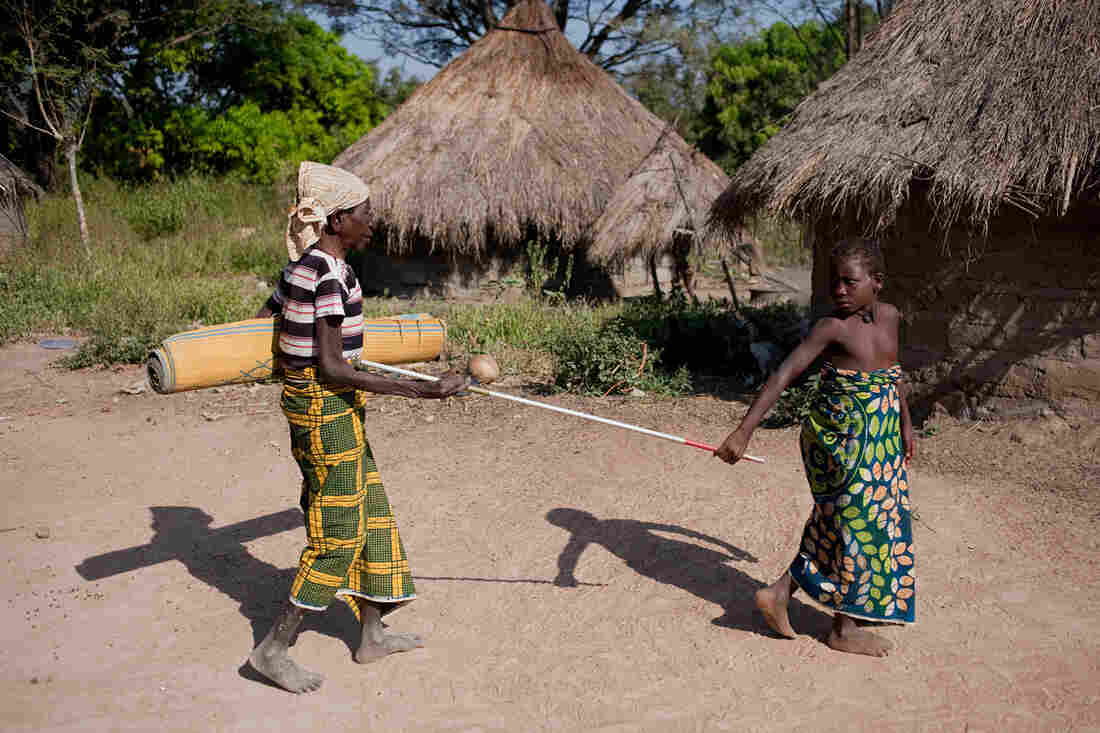 An elderly Nigerian woman who suffers from river blindness is helped by a young girl.