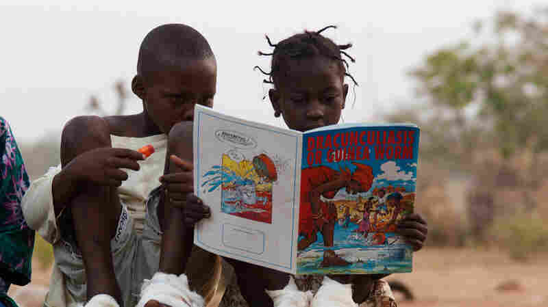 A comic book captures the attention of Guinea worm patients Sadia Mesuna (right) and Fatawu Yakubu at a center for patients in Ghana.