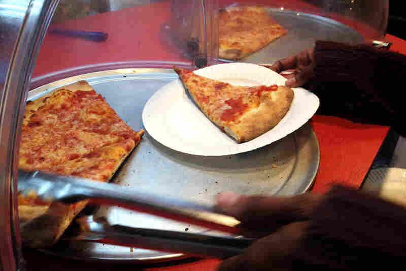 Slices of pizza on the counter of Rosa's Fresh Pizza, where customers are encouraged to pay it forward.