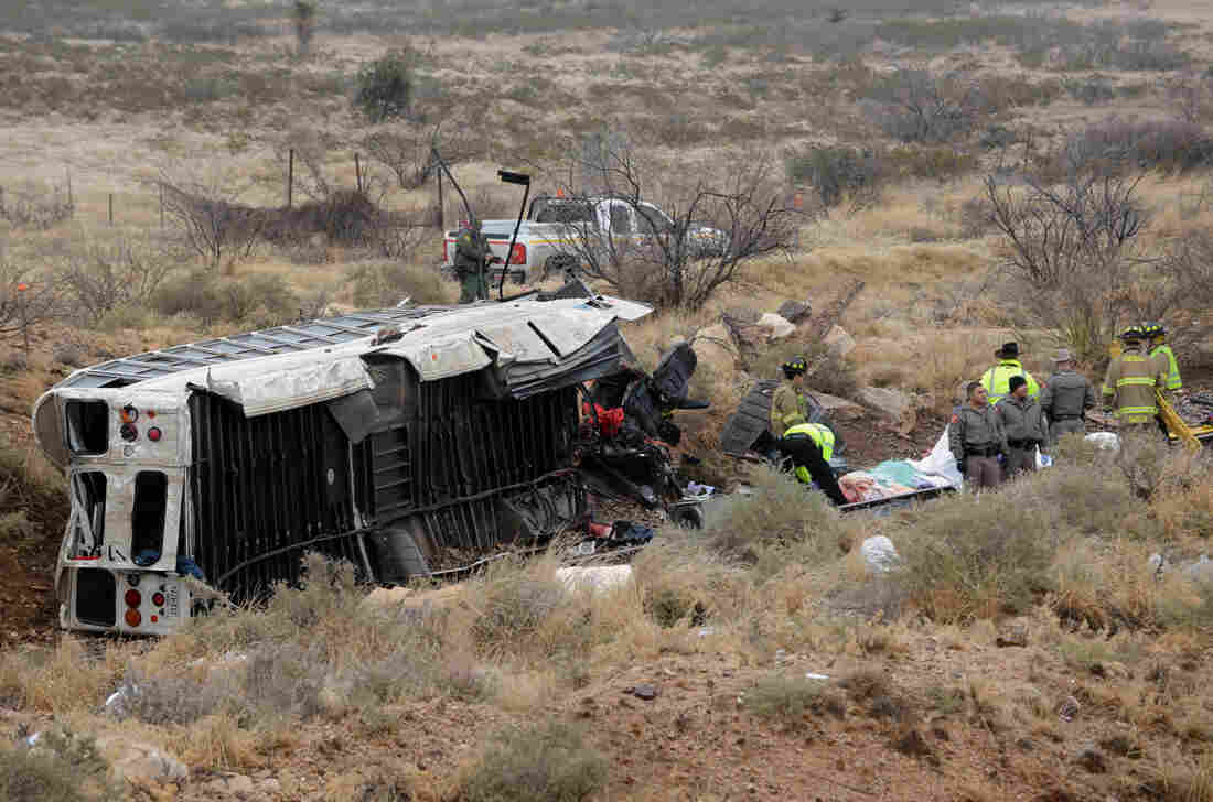 Officials investigate the scene of a prison transport bus crash in Penwell, Texas on Wednesday. Law enforcement officials said the bus carrying prisoners and corrections officers fell from an overpass in West Texas and crashed onto train tracks below, killing at least 10 people.