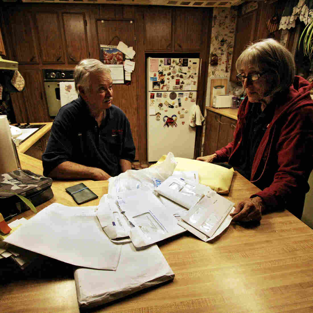Dennie and Kathy Wright sift through a stack of medical bills at their home in Indian Valley, Calif.